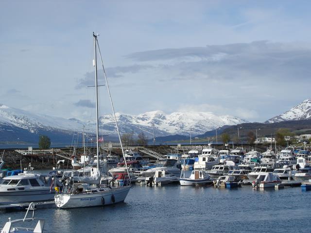 In de haven van Nesna met veel sneeuw op de bergen op de achtergrond