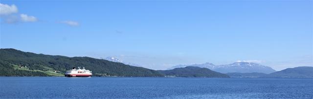Varend in de Solbjergfjorden met een Hurtigrutenboot op de achtergrond