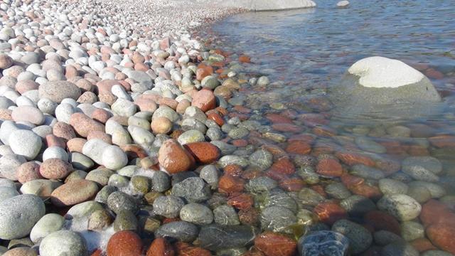 Het water slijpt de kiezels glad