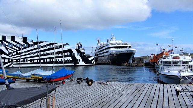 Nog grotere cruiseschepen die niet kunnen afmeren in Lerwick zijn de oorzaak dat jachten plaats moeten maken voor tenders die de cruisegangers aan wal brengen. Links de 'Sans Vitesse' met als haven  'Kootwijkerbroek' op de spiegel.