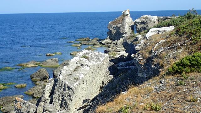 Grote stukken kalksteen zijn afgebrokkeld en liggen op het 'strand'